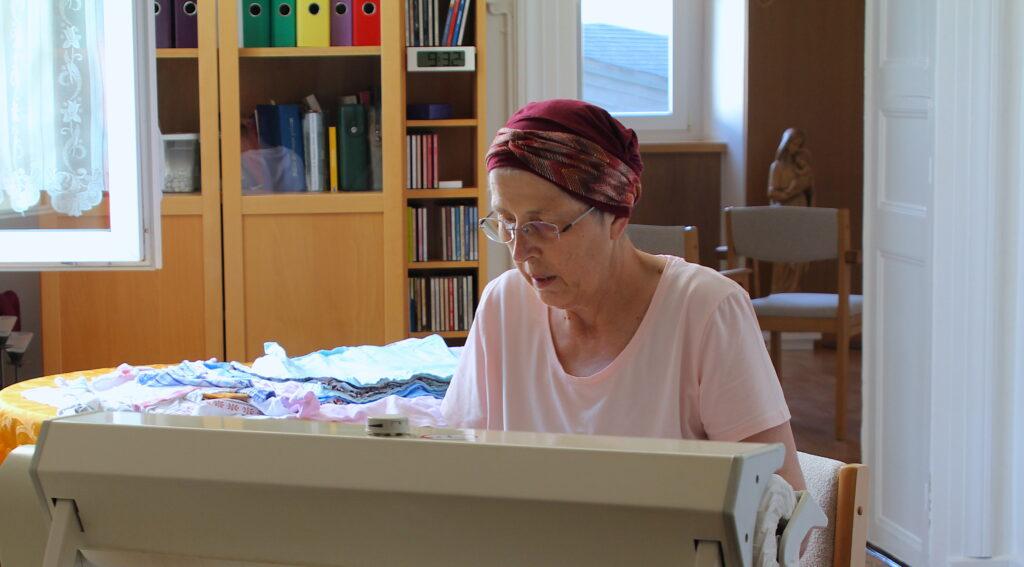 Soeur Irène ist bei der Hausarbeit. Sie lässt Geschirrtücher durch die Mangel, die dann von der 105 Jahre alten Soeur Marie gefaltet werden.